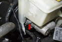 Using a T25 Torx bit socket, remove the brake fluid reservoir mounting bolt (red arrow).