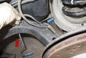 Continue to remove the sensor wiring harness (blue arrow) from the mounts on the trailing arm by pulling it straight out.