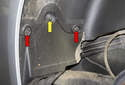 Working at the front of the wheel well liner, remove the two T25 Torx fasteners (red arrows) and the 10mm plastic nut (yellow arrow).