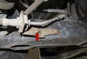 Next, remove 10mm brake hose mounting fastener on the trailing arm (red arrow) located on the inside near drive axle.