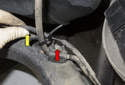 Now back to the top of the trailing arm, pull the wheel speed sensor harness out of the mount (yellow arrow), then remove the 8mm brake line mounting fastener (red arrow).