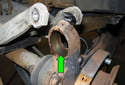 Once ball joint has been removed, clean mounting area of rust and debris (green arrow).