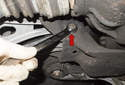 Working at the subframe near the axle and differential, loosen the lower control arm fastener (red arrow).