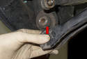 Pull the control arm down and away from the wheel bearing carrier.
