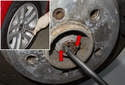 Remove the center cap on rear wheel of vehicle.