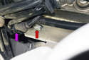 Working at the rear corner of the cylinder head near the camshaft sensor (purple arrow), remove the 13mm heat shield fastener (red arrow).
