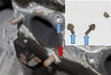 Working above the cylinder head, clean the sealing surface for the gasket using aplastic scraper (red arrow).