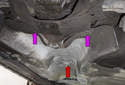 Working at the rear of the exhaust heat shield (red arrow), remove the two 8mm mounting fasteners (purple arrows).