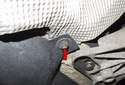 Next, remove the 10mm nut (red arrow) on the heat shield to the Left of the transmission mount bracket.