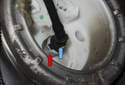 Working at the fuel filter housing, remove the fuel line by pressing the plastic collar (red arrow) toward the filter while pulling the line (blue arrow) straight out.