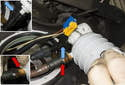 Working at the base of the filer, squeeze the plastic clips together (red arrows) and slide the fuel line off the filter.