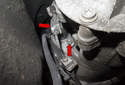 Working at the right side of the transmission, remove the two 13mm slave cylinder fasteners (red arrows).