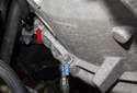 Working at the left side of the transmission, remove E10 (blue arrows) and E14 fasteners (red arrows).