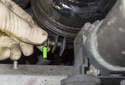 Remove the 10mm reservoir bracket-clamping bolt (green arrow).