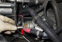Working at the back of the starter, remove the 13mm battery positive (B+) cable nut (red arrow).