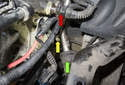 Working behind the alternator just below the oil pressure switch (red arrow), remove the coolant hose to the small coolant pipe (green arrow).