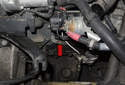 Working below the starter, remove the 10mm fuel line-mounting fastener (red arrow).