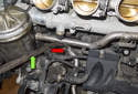 Using a pry bar (green arrow) lever the coolant pipe out of the coolant housing (red arrow).