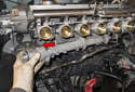 Then remove the upper coolant pipe from the engine, by de-installing the front of the pipe first (red arrow).