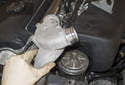 Remove the thermostat housing from the engine by lifting it straight up.