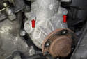 Next, remove the two top 10mm water pump mounting fasteners (red arrows).