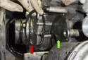 Once the water pump has been removed, clean the sealing surface (green arrow) and discard the old gasket (red arrow).