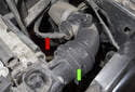 Working at the left side of the radiator, disconnect the upper radiator hose (green arrow) and the vent line (red arrow).