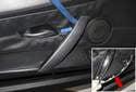Then, using a plastic prying tool, lever the door handle trim piece off the door panel (blue arrow).