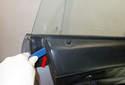 Once the door panel clips have been disconnected, lever the top of the door panel (red arrow) off the door.