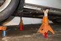 Front: Once you reach the desired height, install the jack stands (red arrows) at the proper jack pad locations to support the vehicle.