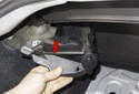 Lift the adjuster up, then slide it toward the inside of the trunk and then toward rear bumper to remove (red arrow).