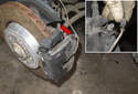 Open the brake caliper bleeder cover and remove the pad wear sensor (red arrow) wire from the mount.