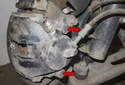 Remove rubber plugs from brake caliper mounting fasteners (red arrows).