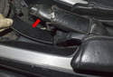 Using a plastic prying tool, lever the plastic trim piece below the parking brake handle (red arrow) out of the center console.