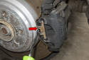 Using a flathead screwdriver, remove brake caliper anti-rattle spring (red arrow) by prying out while securing with hand.
