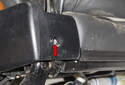 Working at the outer rear corner of the seat, remove the T20 Torx screw (red arrow).
