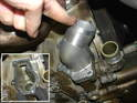 Install the new thermostat in place using a new gasket (lower left).