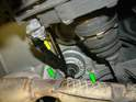 With the transmission supported by your floor jack, carefully remove the nuts that attach the mounts to the chassis (green arrow).