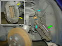Removal of the caliper is accomplished by unbolting the two hex bolts that mount it to the arm (yellow arrow).