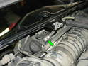 With the top of the engine compartment open, loosen and disconnect the cable that attaches to the alternator.