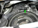 From inside the wheel well, locate the small plastic pull tab located on the water pump friction wheel (green arrow).