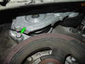 (R50 Cooper) Remove the 10mm bolt at the bottom of the belt tensioner (green arrow).