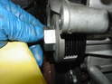 Unscrew the bolt from the tool and place the grooved section of the tool over the stock pulley.