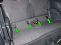 Remove the four child seat latch covers in the rear seat of the car (green arrows).