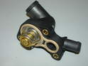 Shown here is the thermostat with gasket mounted in the thermostat housing, ready for installation.