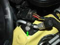 Remove the 10mm bolt securing the radiator fan electrical connection at the front of the driver's side frame rail (green arrow).