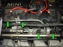 Remove the electrical plug going to each fuel injector by pressing the small metal clip in and pull the plug off each injector (green arrows).