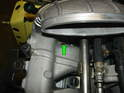The green arrow shows the mounting location of the fuel volume valve vacuum hose at the intake manifold.