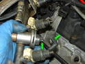 As you remove the fuel rail from the car, you can see how the vacuum hose connects to the underside of the fuel pressure regulator (green arrows).