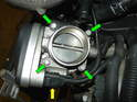 Remove the four 10mm bolts securing the throttle body to the intake tube (green arrows).